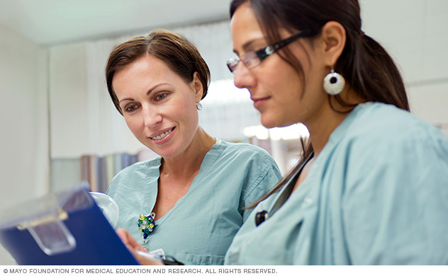 Obstetric-gynecology nurses review a care plan.