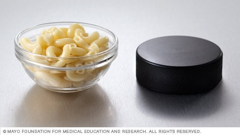 Half a cup of pasta next to a hockey puck