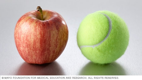 A small apple next to a tennis ball