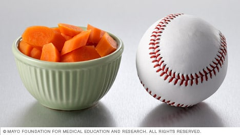 Half a cup of cooked carrots next to a baseball
