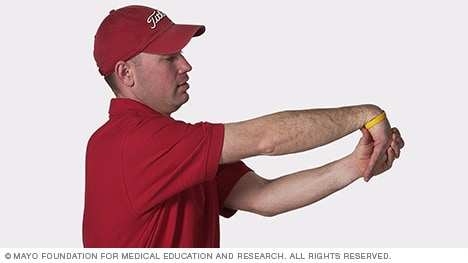 Photo of man stretching the wrist muscles downward