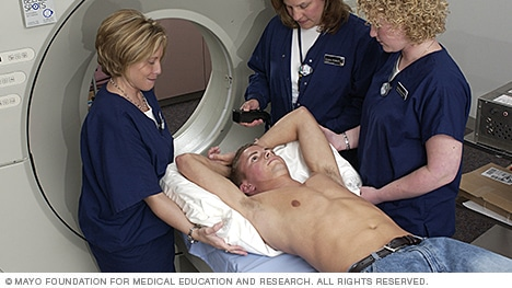 Photo of a man lying down, surrounded by radiation therapy team