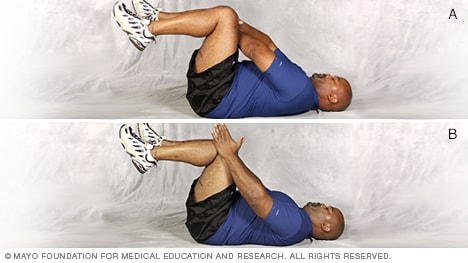 Photo of man doing variations of double-leg abdominal press core-strength exercise