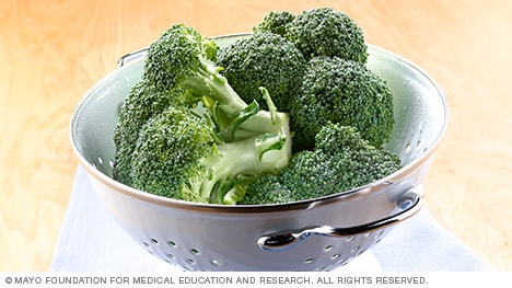 Raw broccoli crowns in a colander