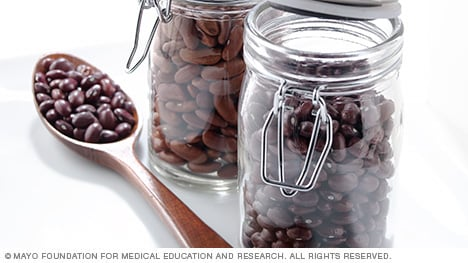 A spoon next to jars of dried beans
