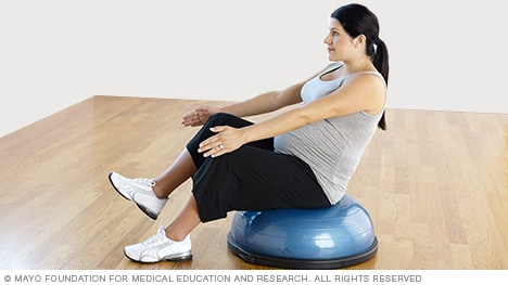 Pregnancy exercises — pregnant woman practicing a one-leg v-sit with a Bosu Balance Trainer