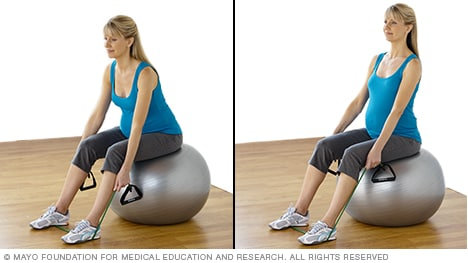Pregnant woman practicing seated dead lift with resistance tubing