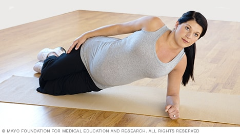 Pregnancy exercises — pregnant woman practicing modified side plank