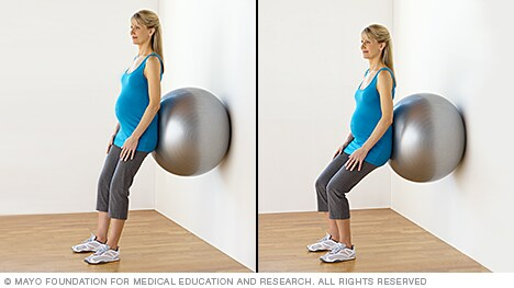 Pregnant woman practicing squats with a fitness ball