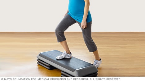 Pregnant woman practicing step-up exercise