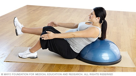 Pregnancy exercises — pregnant woman practicing a v-sit supported by a balance trainer