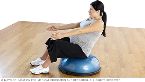 Pregnant woman practicing v-sit seated on a Bosu Balance Trainer