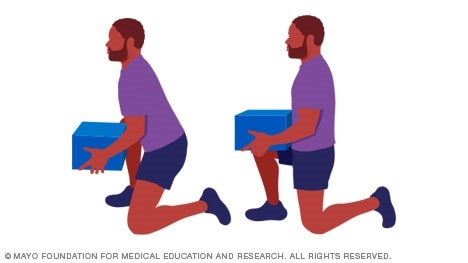 Photo of man lifting box to his knee
