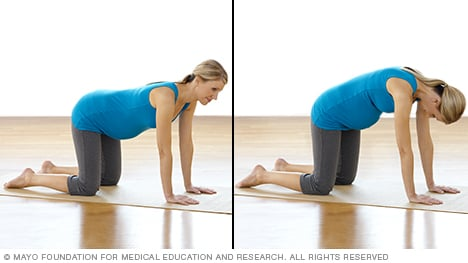 Pregnancy stretches — pregnant woman practicing low back stretches