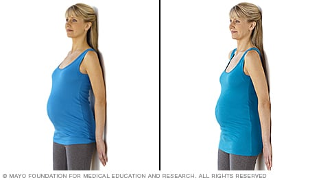 Pregnancy stretches — pregnant woman practicing standing pelvic tilt