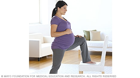 Woman in labor lunging against a chair