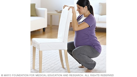 Woman in labor squatting against a chair