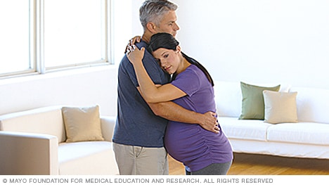 Woman in labor swaying with partner