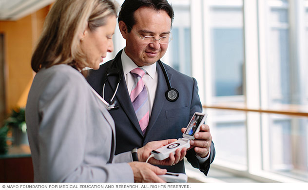 Two doctors consult over a handheld cardiac monitoring device.