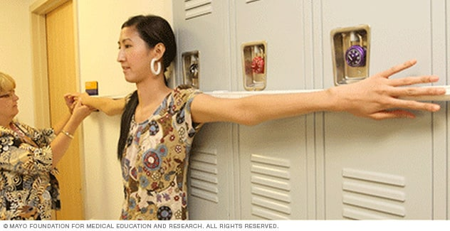 Young woman having the length of her arm span measured