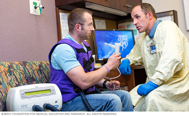 A doctor with a person wearing a vest for vest therapy