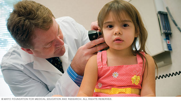 A doctor examines a girl's ear during a family medicine visit.