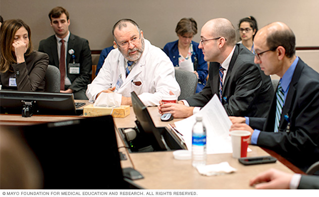 Experts discuss complex kidney tumor cases at a tumor board meeting.