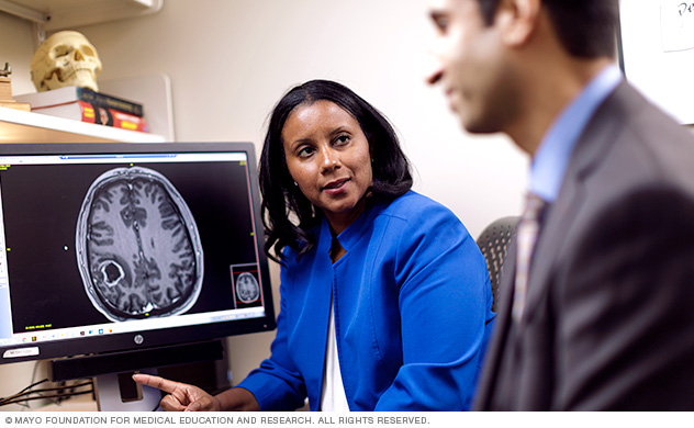 Doctors who specialize in treating brain tumors discuss a patient's scan.