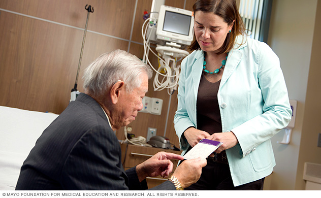 A Mayo Clinic neurologist converses with a man about a possible carotid artery disease diagnosis.