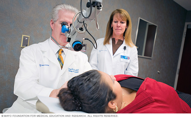 A doctor who specializes in the diagnosis and treatment of ear, nose and throat conditions (otorhinolaryngologist) examines a patient.