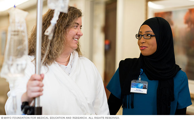 A patient and Mayo Clinic staff person walk down a Suites at Saint Marys hallway.