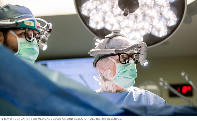 Two surgeons look at a monitor during surgery.
