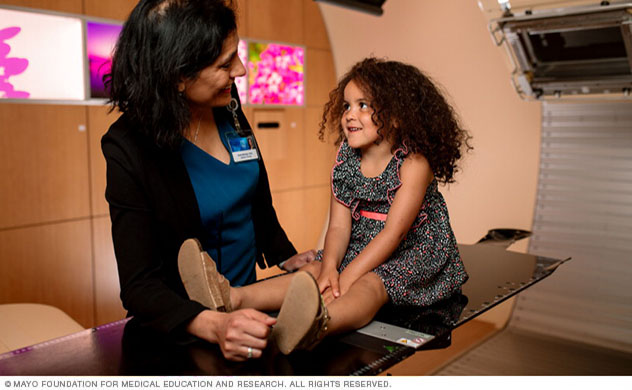 Proton beam medical director cares for a child in a treatment room.