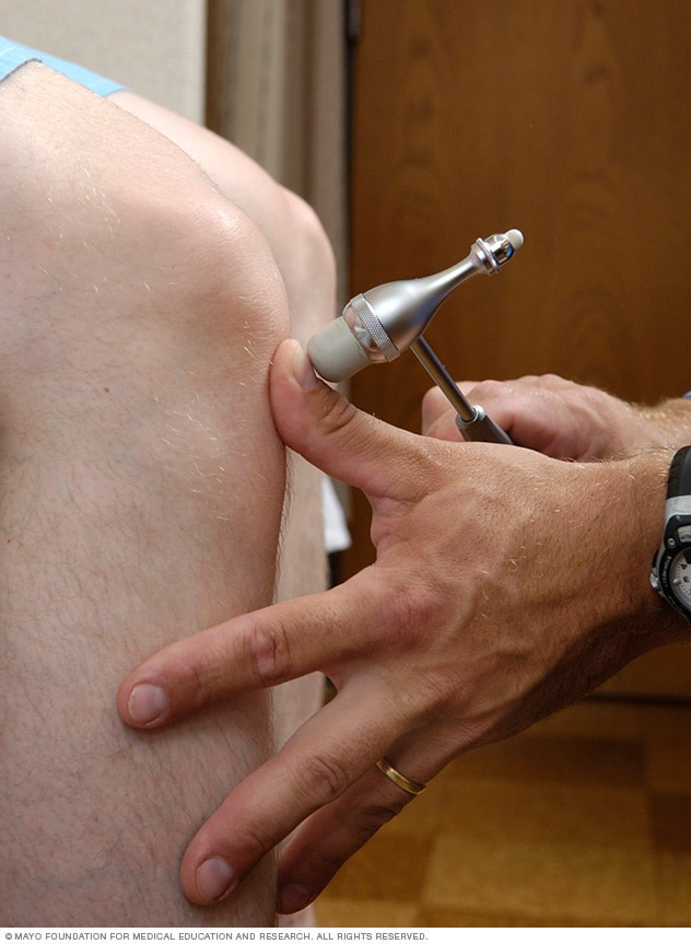 Neurological exam checking knee reflexes
