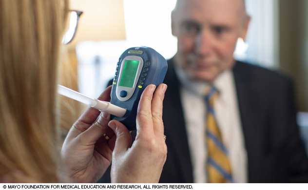 A tobacco cessation counselor monitors someone using a carbon monoxide screening device.