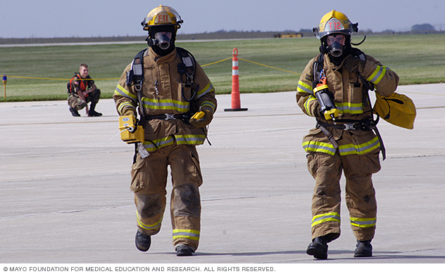 Safety workers in fire gear move across a tarmac.
