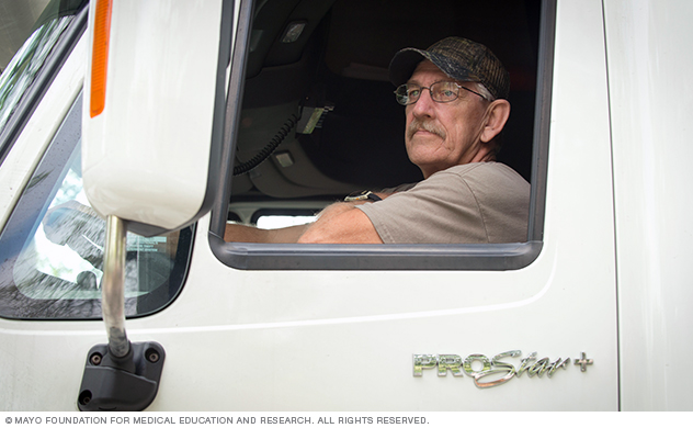 A driver sits in a semi tractor awaiting instruction.