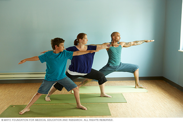 Three people performing a yoga pose while standing