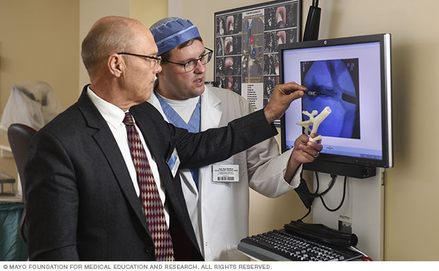Doctors review an image and 3D model.