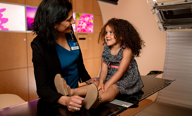 Radiation oncologist talks with pediatric cancer patient.