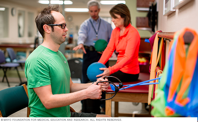 A young man works with pain rehabilitation exercise equipment.