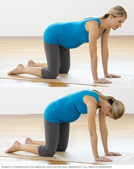 Photo of pregnant woman practicing the low back stretch