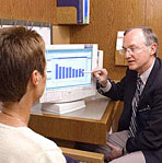 Doctor pointing to computer monitor as he talks to a patient
