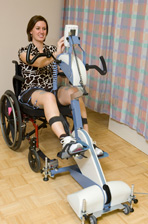 A patient exercises paralyzed leg muscles with a functional electrical stimulation bike.