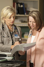 Photo of two nurse practitioners reviewing a patient chart