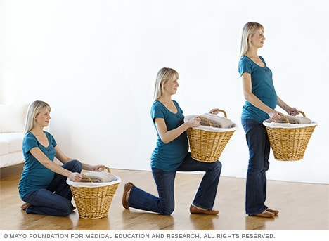 Photo of pregnant woman lifting basket from floor