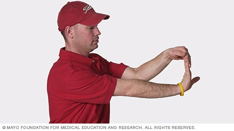 Photo of man stretching the wrist muscles upward
