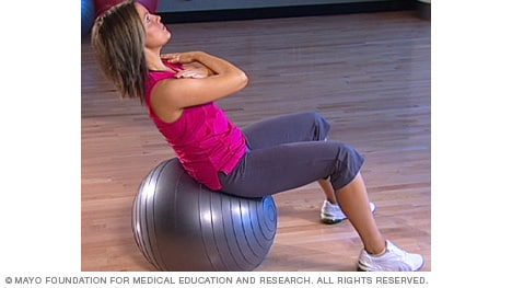 Photo of woman doing abdominal crunch exercise on fitness ball