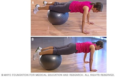 Photo of woman doing advanced plank with fitness ball