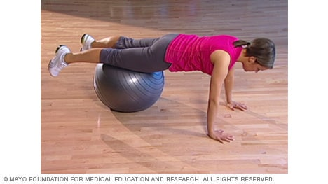 Photo of woman doing plank with fitness ball